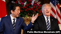 U.S. President Donald Trump (right) and Japanese Prime Minister Shinzo Abe talk in Florida on April 17.