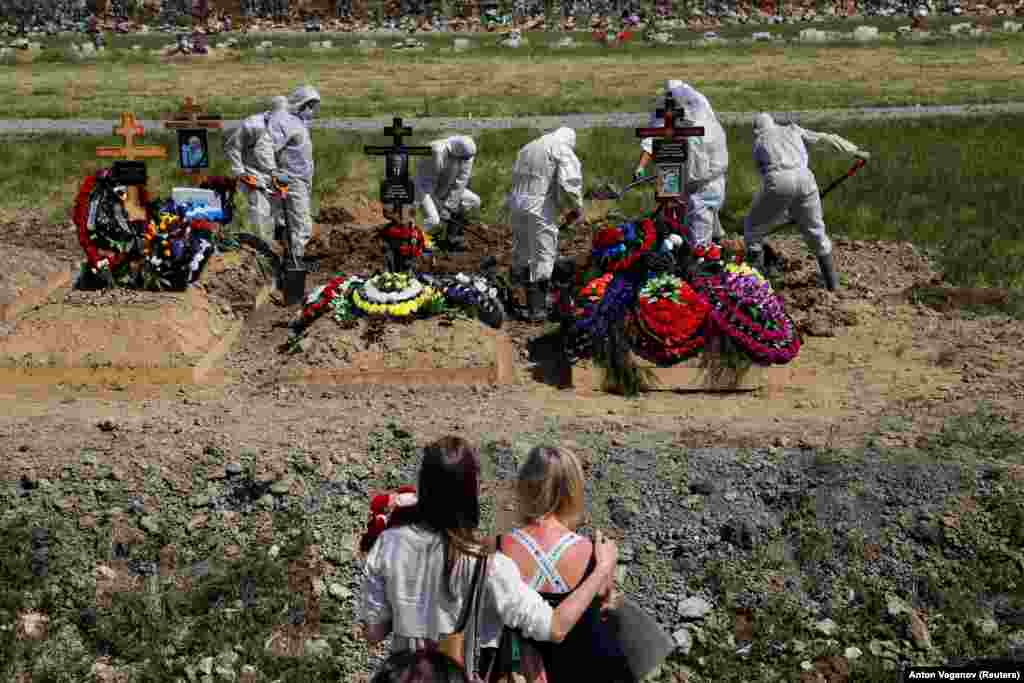 Mourners watch gravediggers burying a person who presumably died of COVID-19 in the special-purpose section of a graveyard on the outskirts of St. Petersburg, Russia. (Reuters/Anton Vaganov)