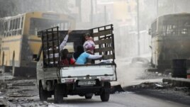 Syria -- A family on a pick-up truck flees violence in the city of Aleppo, 17Oct2012