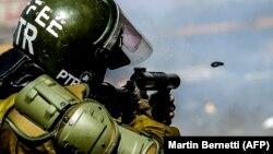 اعتراضات مرگبار شیلی تا کنون بیش از ۲۰ کشته برجای گذاشته است؛ در تصویر یک عضو پلیس ضدشورش در حال شلیک اشکآور است.