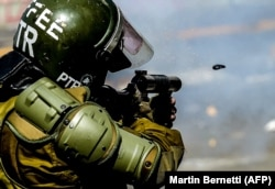 Полицейский стреляет газовыми гранатами в толпу манифестантов в Сантьяго. Чили, 21 октября