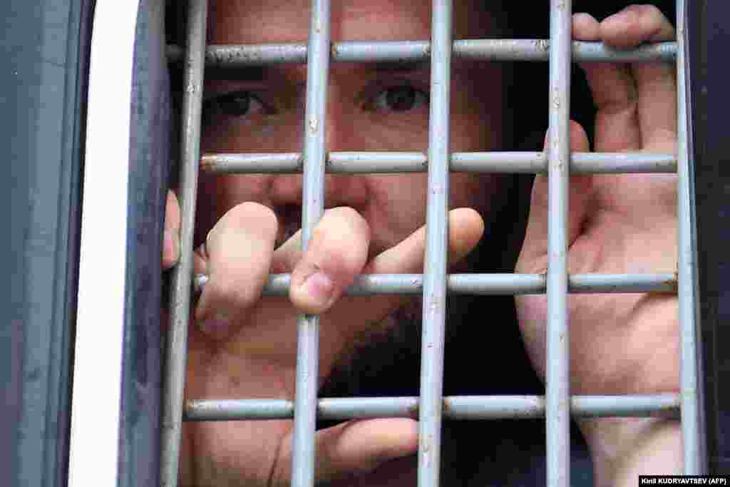 A detained protester looks out from the barred window of a police van.