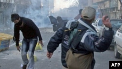 Protesters throw stones at riot police during an antigovernment demonstration in Tehran on February 14.
