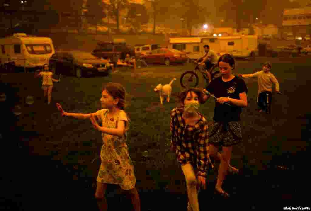 Дети играют на улице окутанного дымом городка в Новом Южном Уэльсе. Этот регион – один из наиболее пострадавших от пожаров. Там сгорело около пяти миллионов гектаров леса и 1300 домов. Тысячи людей были вынуждены покинуть свое жилье