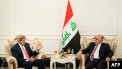 U.S. Secretary of State John Kerry (left) speaks with new Iraqi Prime Minister Haidar al-Abadi in Baghdad on September 10.