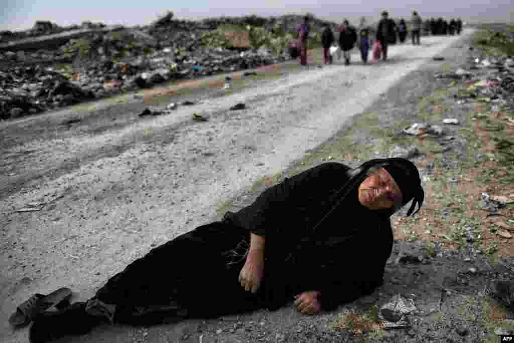 An Iraqi woman lies on the ground as civilians flee Mosul while Iraqi forces advance inside the city during fighting against Islamic State militants. (AFP/Aris Messinis)
