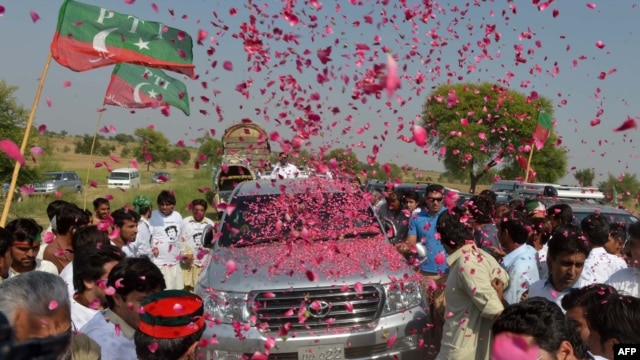 Pakistanis welcome the convoy of cricket star turned politician Imran Khan on his rally toward the tribal areas in Mianwali on October 6.