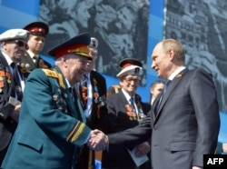 Vladimir Putin shakes hands with a World War II veteran during Victory Day celebrations in 2015,