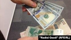 Банкноты номиналом сто долларов, сто и один сомони.