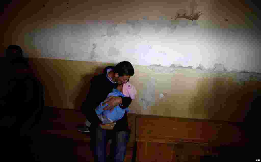 A man kisses his baby at a room in a temporary refugee camp in Vrazdebna, Bulgaria. (epa/Vassil Donev)
