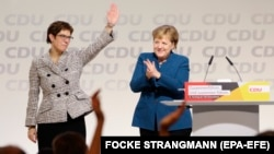 Annegret Kramp-Karrenbauer (left) waves next to German Chancellor Angela Merkel after taking over CDU party leadership in December 2018.