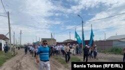 Приехавшие на поминки по Дулату Агадилу люди идут на кладбище, где он похоронен. Село Талапкер Акмолинской области, 8 августа 2020 года.