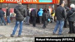 Банк алдында кезекте тұрған жұрт. Алматы, 20 ақпан 2014 жыл.