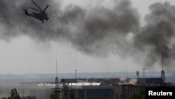 A Ukrainian Mi-24 helicopter gunship fires its cannons at rebels at the main terminal building of Donetsk's international airport on May 26.