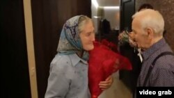 Babushka Lida meets her idol, singer Charles Aznavour, backstage in a Moscow concert hall.