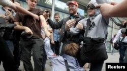 """Люди тащат активиста ЛБГТ-сообщества, выступившего против поправок в закон о запрете """"пропаганды гомосексуализма"""". Москва, 11 июня 2013 года."""