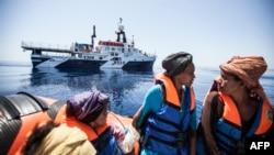 Жерорта теңізінде қайықпен келе жатқан мигранттар мен оларды құтқаруға жеткен кеме.
