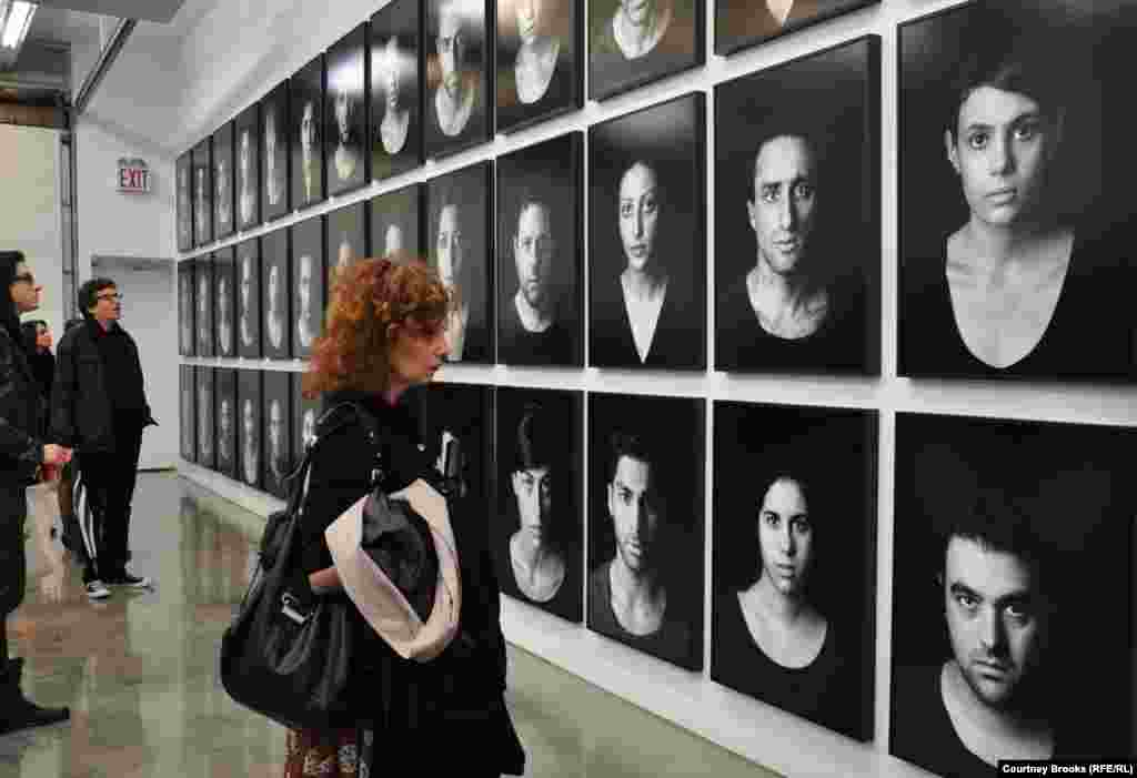 "A woman surveys pictures of ""The Masses,"" Shirin Neshat's depiction of those affected by oppression, protests, and civil unrest."