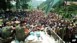 Dutch UN peacekeepers sit on top of an armored personnel carrier while Muslim refugees from Srebrenica gather in the village of Potocari, just north of Srebrenica, on July 13, 1995.