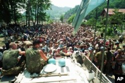 Dutch UN peacekeepers sit on their armored vehicle as a crowd of Muslim refugees from Srebrenica gathers on July 13, 1995.