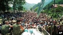 Холандските мировници на ООН седат на нивното оклопно возило додека толпа муслимански бегалци од Сребреница се собира на 13 јули 1995 година.