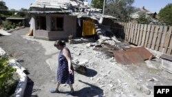 Жінка біля зруйнованої будівлі на Донбасі, архівне фото
