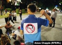 Парламенттің бұрынғы спикерінің суреті ілінген футболка киген адам.