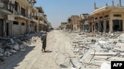 A Syrian man inspects the damage in the town of Khan Sheikhun in Idlib Province in August.