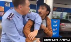 Полицейский пытается увести задержанного активиста Болатбека Блялова. Астана, 16 июня 2015 года.