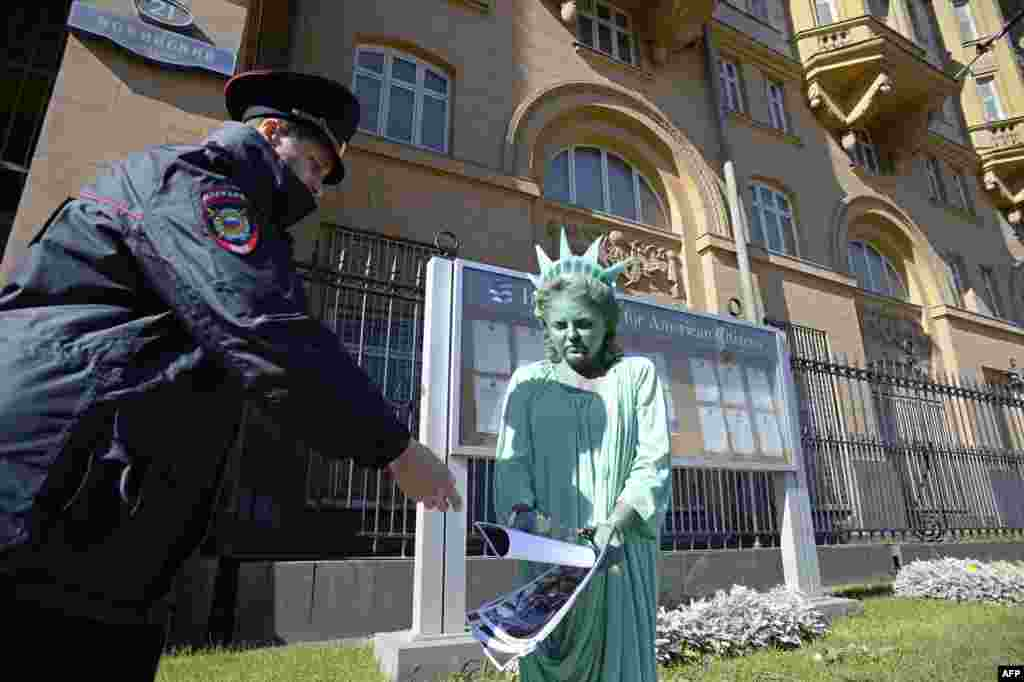A woman passes photographs of riots in the United States to a Russian policeman while wearing a Statue of Liberty costume during a protest in front of the U.S. Embassy in Moscow. (AFP/Aleksandr Nemenov)