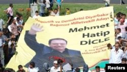 Supporters of the Peace and Democracy Party (BDP) carry an election banner of independent candidate Hatip Dicle during a protest against the election board in Diyarbakir on June 23.