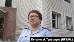 Полиция өкілі Ғалия Тоқмырзина өртенген үйдің алдында тұр. Алматы облысы, 17 шілде 2012 жыл.