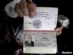 Кәси әби үзенең паспортын күрсәтә
