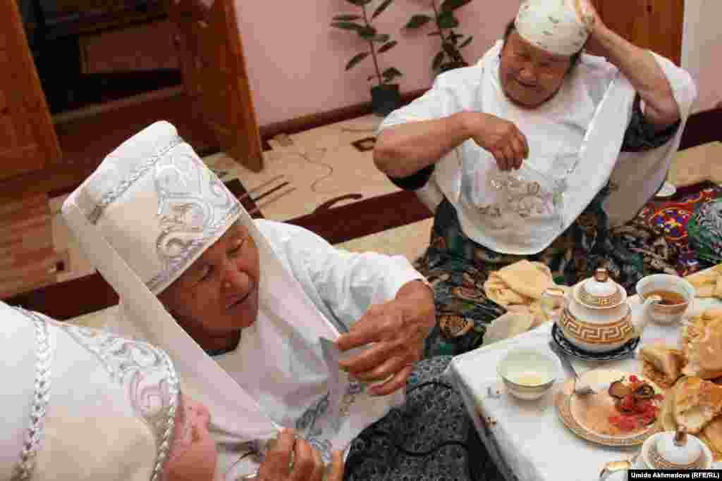 Гости Азизы примеряют головные уборы, им скоро предстоит выступать как фольклорной группе. Женщины радуются предстоящему выступлению, ибо до этого они всегда пели в своем кругу.