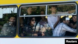 Gay-rights activists look out from a bus as they are evacuated by police during clashes in Tbilisi on May 17.