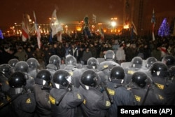 Riot police block demonstrators trying to storm the government building in Minsk on December 19, 2010.