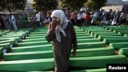 Bosnia-Herzegovina -- Bosnian Muslim woman cries near coffins prepared for a mass burial at the Memorial Center in Potocari, near Srebenica, 11Jul2011