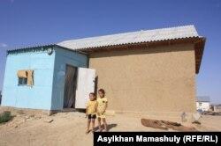 Байқоңыр маңындағы Ақай ауылындағы үйлердің бірінің алдында тұрған балалар. Қызылорда облысы, 14 шілде 2013 жыл.