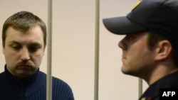 Mikhail Kosenko (left), one of the activists accused of violence at a rally on the eve of President Vladimir Putin's inauguration, stands in a defendant's cage in a court in Moscow in October 2013.