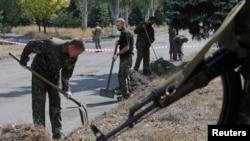 Пленные украинские военные под надзором вооруженных сепаратистов очищают улицу. Донецкая область, 29 августа 2014 года.
