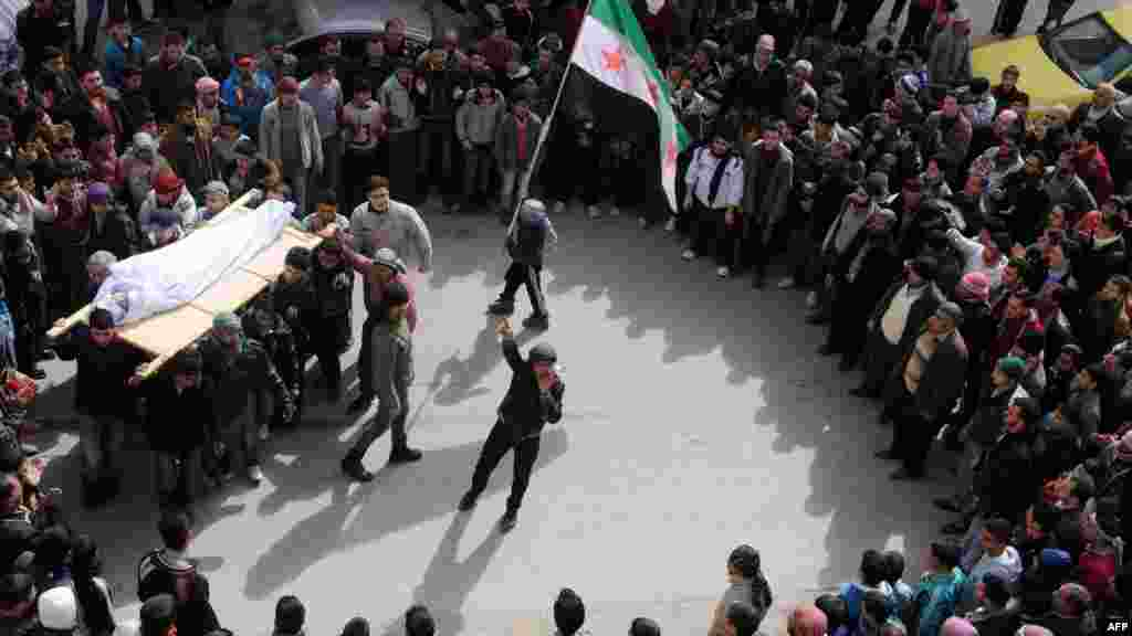 Syrian mourners, one carrying the pre-Ba'ath national flag adopted by the rebel movement, carry the body of a youth reportedly killed in violence in Idlib before his burial on February 23. (AFP PHOTO/BULENT KILIC)
