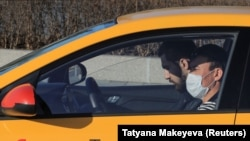 A driver from the Yandex.taxi ride-sharing service sits inside his car in Moscow on March 26. One driver said he and his colleagues have been encouraged to disinfect the interiors of their vehicles but that there have been no instructions on how often the cars should be disinfected, and no one is checking to see that it is done at all.