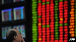 Мужчина наблюдает за котировками ценных бумаг на Шанхайской бирже.