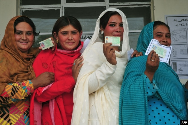 Pakistani voters pose with their national identity cards as they queue to cast their ballots at a polling station in Rawalpindi.