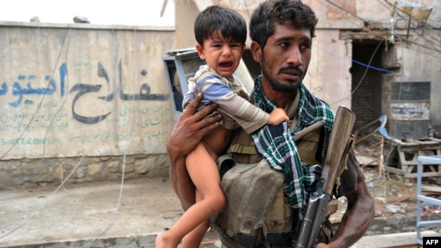 An Afghan policeman carries a traumatized child at the site of a suicide car-bombing in front of the Indian consulate in Jalalabad on August 3.