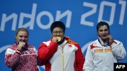 U.K. - China's Zhou Lulu (C) poses on the podium with her gold medal, next to Russia's Tatiana Kashirina (L) silver medal, and Armenia's Hripsime Khurshudyan (R) bronze medal, during the women's 75+kg group A weightlifting event, 05Aug2012