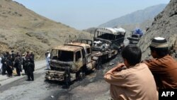 Pakistani security personnel gather beside torched NATO supply trucks after an attack by armed militants in the northwestern Khyber district in June.