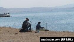 Каспий теңізі жағасында балық аулап отырған адамдар. (Көрнекі сурет).
