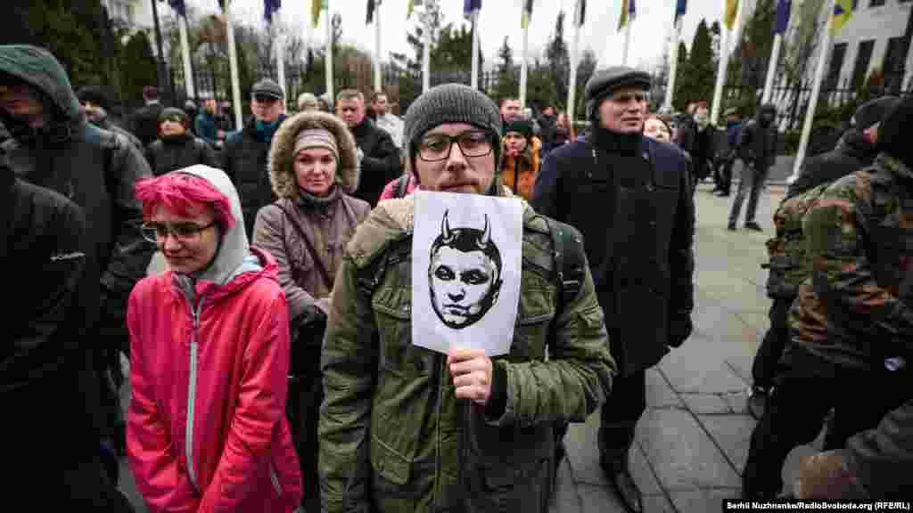 Активіст тримає плакат із зображенням голови МВС Арсена Авакова, стилізованого під чорта