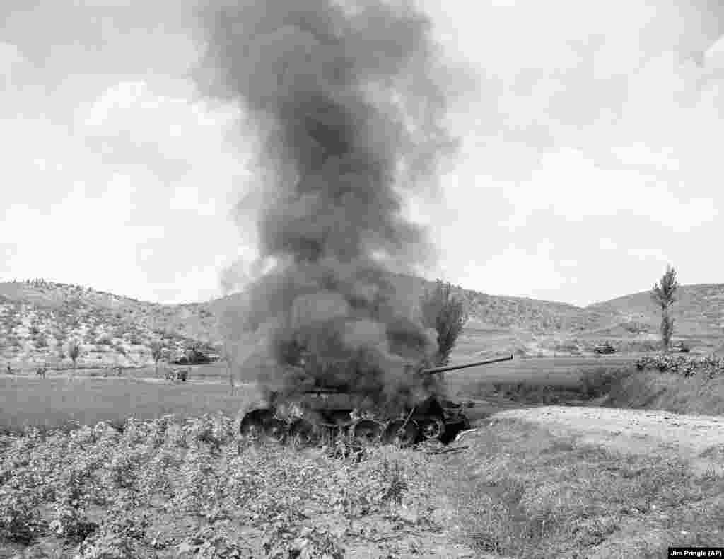 A Soviet-made North Korean T-34 on fire after being hit by an American tank during the Korean War, September 9, 1950.